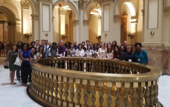 The conference participants are posing for a group photo in the lobby of the State Capitol building.